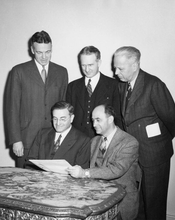 Photograph by Lionel Heymann of Robert Maynard Hutchins, University of Chicago president (1929-1945) and chancellor (1945-1951), with team members of the Manhattan Project, the program established by the United States government to build the atomic bomb. Standing, from left: Mr. Hutchins, Walter H. Zinn, and Sumner Pike; seated: Farrington Daniels, and Enrico Fermi. University of Chicago Photographic Archive, [apf digital item number, e.g., apf12345], Special Collections Research Center, University of Chicago Library. accessed at http://photoarchive.lib.uchicago.edu/db.xqy?one=apf1-05063.xml